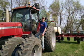 Male Agriculture student standing on the step of a red CASE tractor with a planter attached.