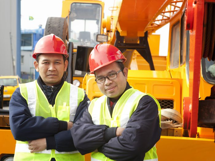 Construction workers posing next to the huge mobile crane
