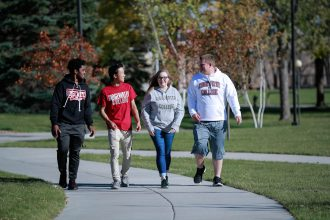 Four students, three male and one female, walk on a campus sidewalk